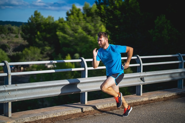 Man with blue shirt running on a road surrounded by nature