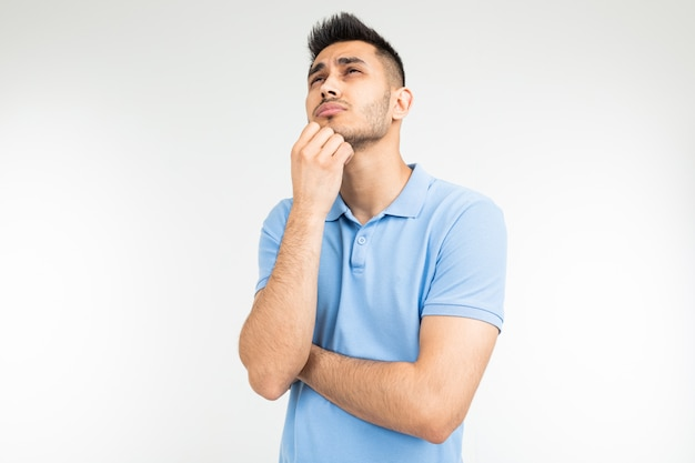 Man with a blue t-shirt thoughtful on a white studio