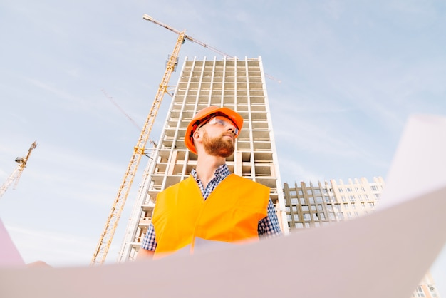 Man with blueprint looking away