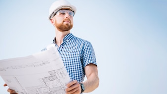 Man with blueprint looking away