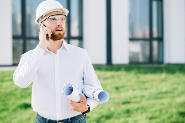 Man with blueprints talking on phone