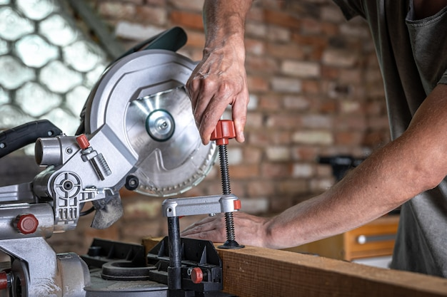 A man with a board and miter saw close up, concept building and repair.