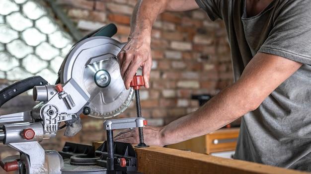Un uomo con una tavola e una troncatrice da vicino, costruzione di concetti e riparazione.