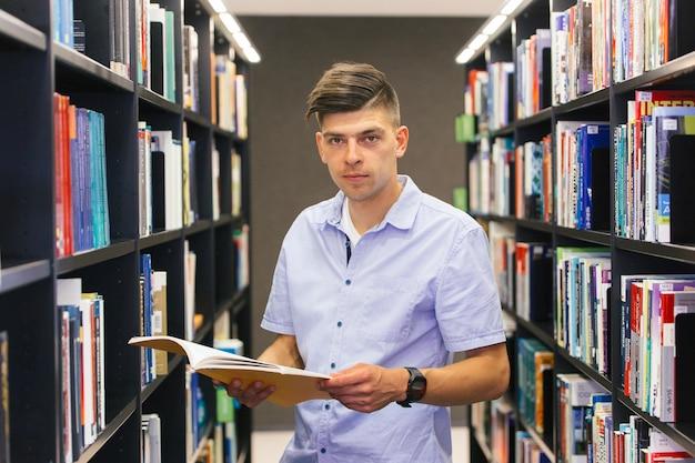 Man with book between bookshelves