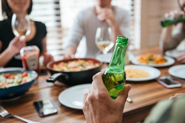 座っていると友達と祝っているビールのボトルを持つ男