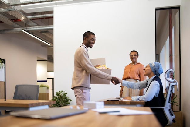 Man with box of belongings being introduced to coworkers at his new job