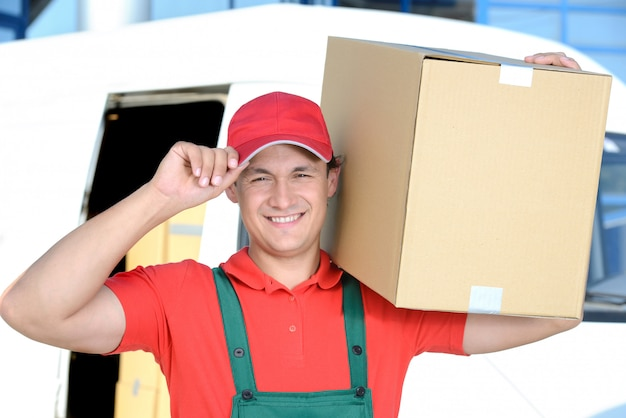 Man with a box on his shoulder carries a delivery for a man.