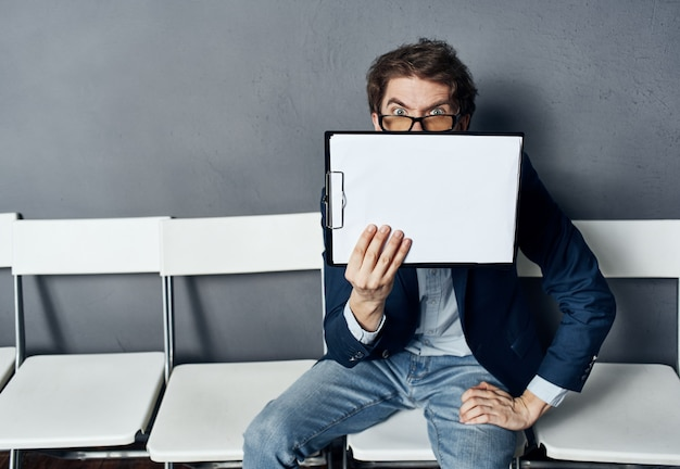 A man with a box sits on a chair with things documents dismissal