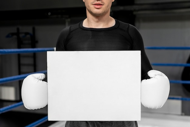 Man with boxing gloves holding pape sheet