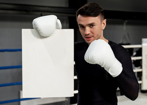 Man with boxing gloves holding paper sheet