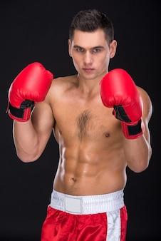 Man with boxing gloves is posing