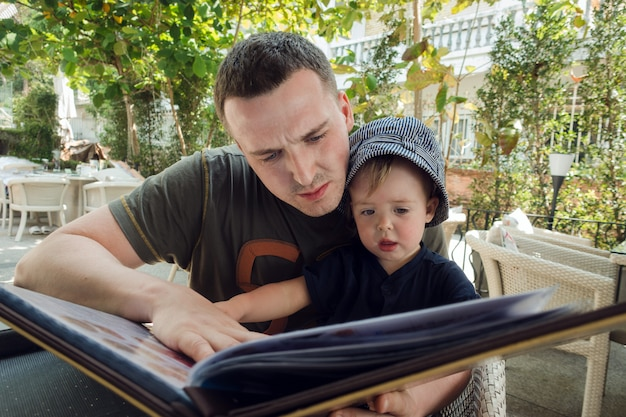 Man with boy exploring book on terrace