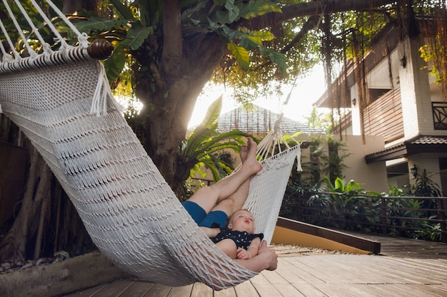 Man with boy lounging in hammock