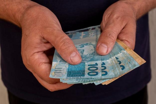 手にブラジルのお金を持つ男