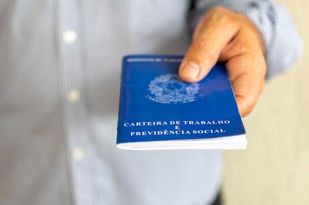 ブラジルのワークカードを持つ男。雇用と給与の増加の概念。