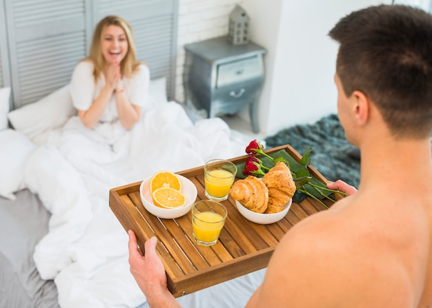 Man with breakfast on board near happy woman in bed