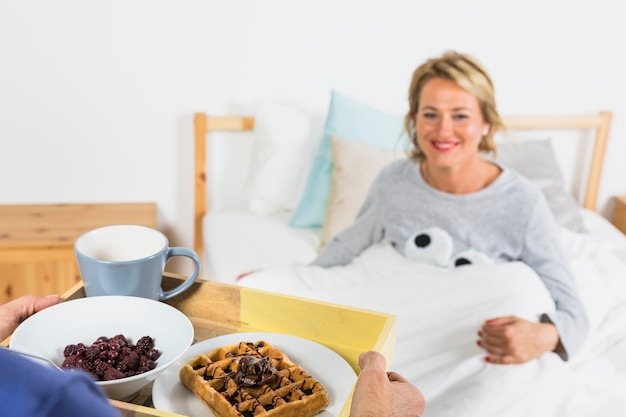 Man with breakfast near aged smiling woman in duvet on bed