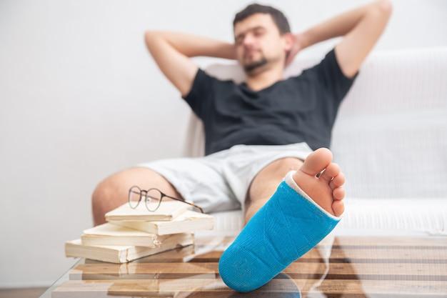 自宅のリハビリテーションで本を読んで足首の捻挫による怪我の治療のための青い副子で足を骨折した男性。