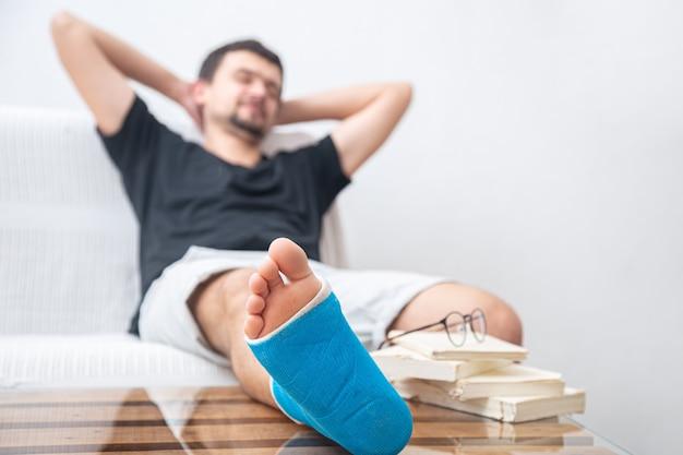 Мужчина со сломанной ногой в синей шине для лечения травм от растяжения связок голеностопного сустава читает книги в домашней реабилитации.