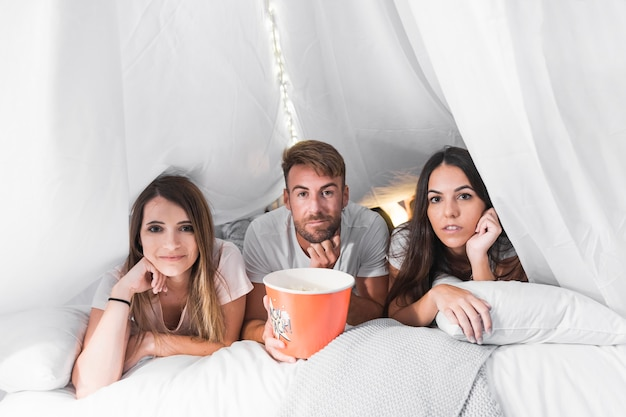 Man with bucket of popcorns lying on bed with two female friends