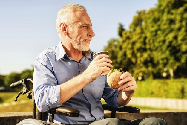 Man with burger and coffee. outdoor rehabilitation.