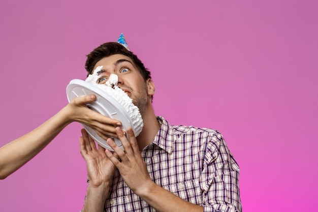 Man with cake on face over purple wall. birthday party.