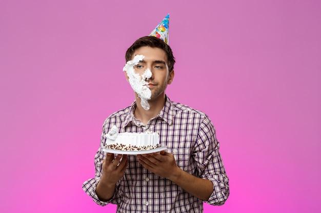 Человек с тортом на лице над фиолетовой стеной. день рождения.