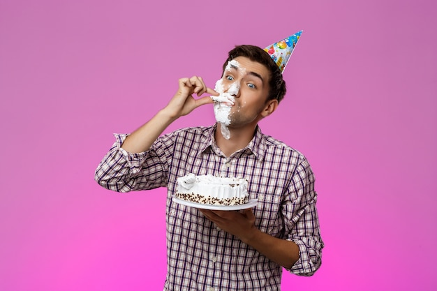 紫色の壁の上の顔にケーキを持つ男。誕生日会。