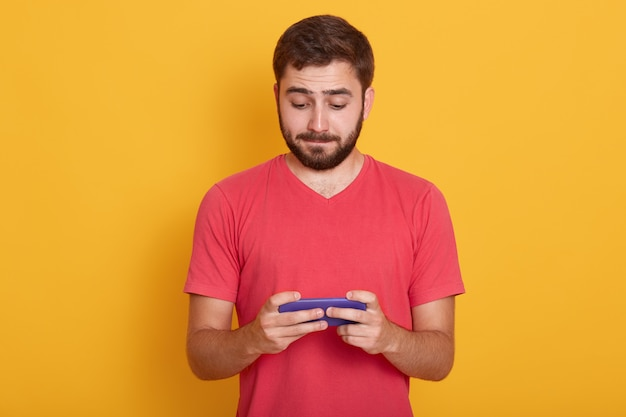 Man with calmfacial expression, dreses red casual t shirt, playing online games on smartphone or checking his social network, posing isolated on yellow. technology concept