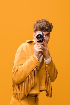 Man with a camcorder in a yellow scene