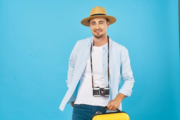 青い背景のトリミングされたビューにカメラと帽子を持つ男