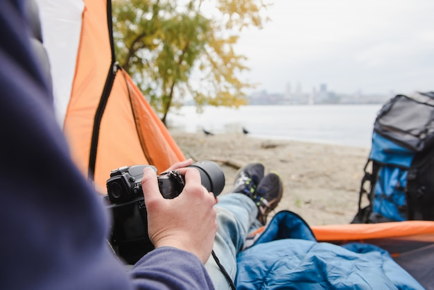 Man with a camera in camping tent