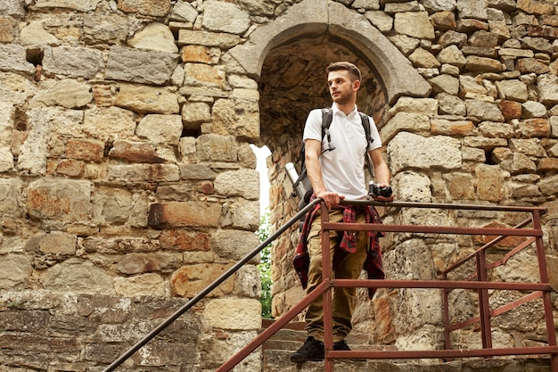 Uomo con la macchina fotografica sulle scale del castello