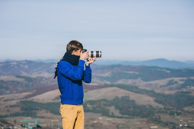 Man with a camera at the edge of a cliff overlooking the mountains below