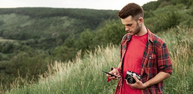 自然の中でカメラを持つ男