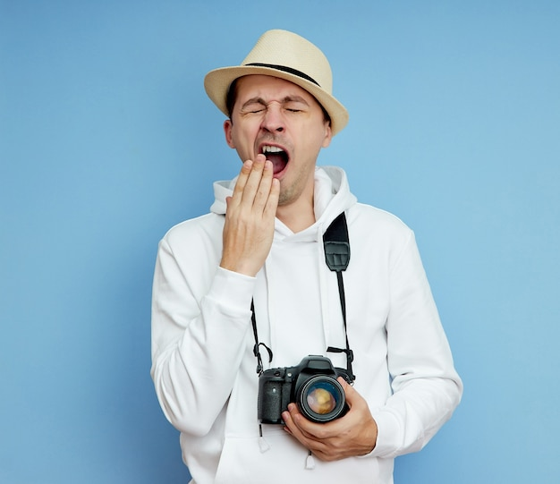 Man with the camera is tired and yawns