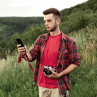 Uomo con fotocamera e cellulare