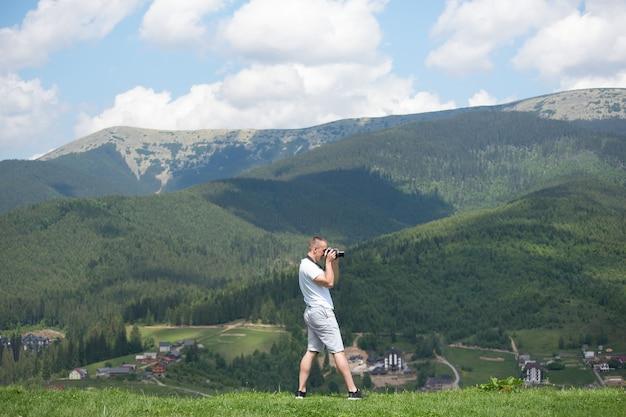 丘の上に立って自然を写真に撮るカメラを持つ男。夏の日