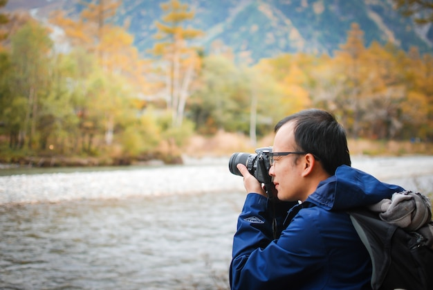 Man with camera and taking photos,sit near the natural wind river with autumn forest