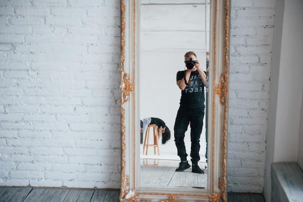 Uomo con la macchina fotografica che cattura un colpo nello specchio vintage. la ragazza si sta divertendo dietro