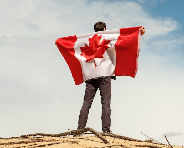 A man with a canadian flag stands on the sand, skies on the background.