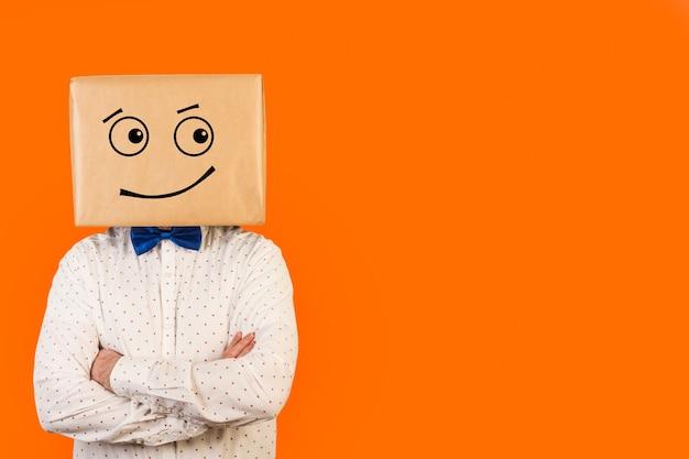 Человек с картонной коробкой на голове с улыбающимся жестом на оранжевой стене