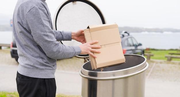 Человек с картонными коробками в бумажном депозите для переработки.