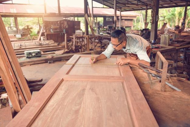 Человек с концепцией строительства инструментов плотников. плотник работает на деревообрабатывающих станках в столярной мастерской. винтажном стиле