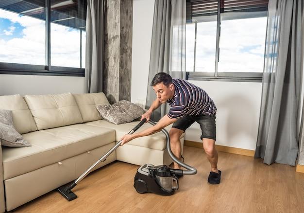 평상복을 입고 거실 소파 아래에서 진공 청소기로 청소하는 남자. 전신.