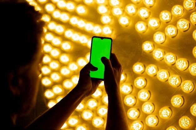 Человек с мобильным телефоном перед стеной желтого света