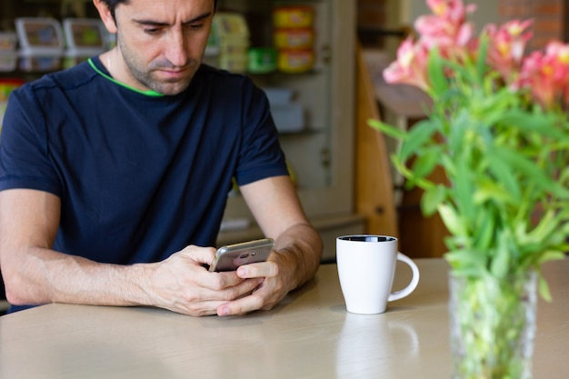 テーブルの上に携帯電話と側面にコーヒーカップと花瓶を持つ男ストレスの多いライフスタイルの概念