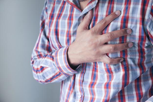Человек с болью в груди на сером фоне