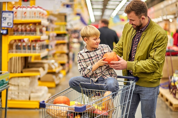 食料品店でグレープフルーツを選ぶ子供男の子を持つ男、息子はカートに座って、話し合う