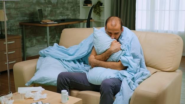 Covid-19 잠금 동안 담요로 싸인 소파에 오한을 가진 남자.